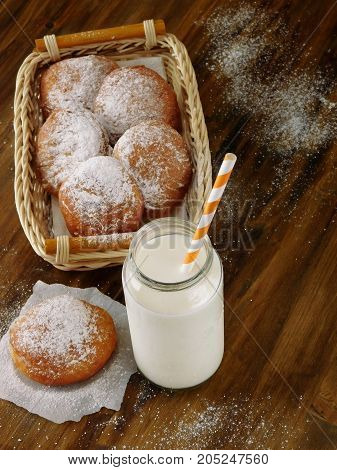 Doughnut and a glass jar of milk with a straw on a wooden table