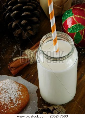 Milk in a glass jar with a straw. Christmas attributes in the background. View from above