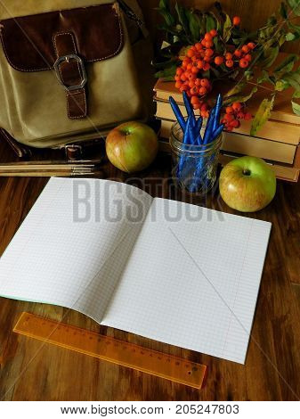 Open paper notebook with school supplies and apples in the background. The notebook is lying on a wooden table