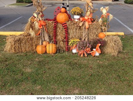 Hay bale with Autumn decoration with happy straw people and pumpkins on a sunny day