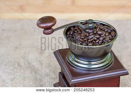 Top part of coffee grinder full of roasted coffee beans