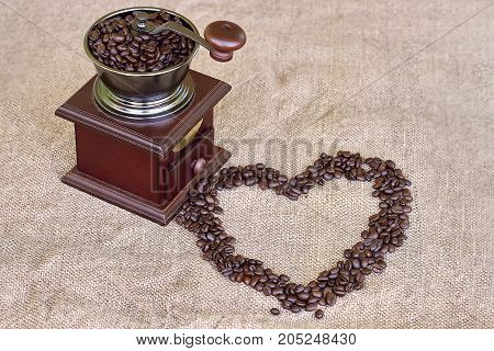 Coffee grinder full of roasted coffee beans and coffee beans heart shape