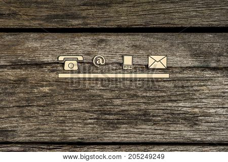 Contact and communication icons telephone at sign mobile and mail on textured rustic wooden boards.
