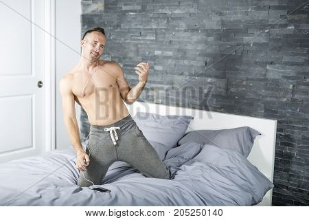 A Young man in bed playing air guitar