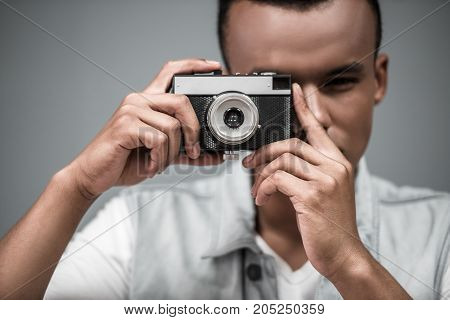 Stylish Afro American guy is using a photo camera on gray background