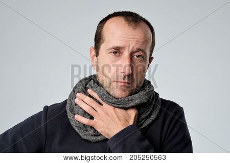 Caucasian man in scarf with headache and sore throat has cold. He is looking sadly at camera, holding hand near neck