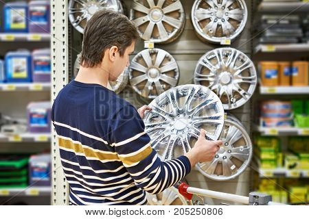 Man Chooses Alloy Wheels For Your Car Wheels In Supermarket