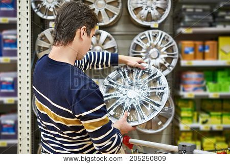 Man chooses alloy wheels for your car wheels in the supermarket poster