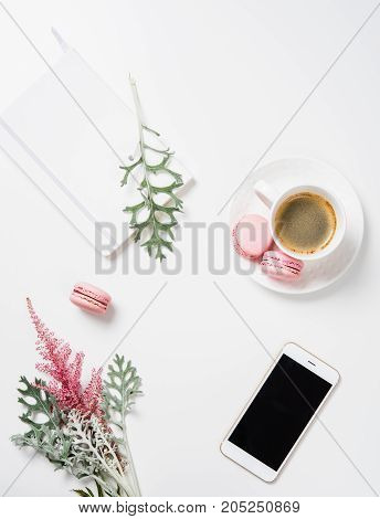 Social media flat lay with coffee, pink macaroons, flowers and smartphone on white background