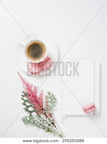 Social media flat lay with coffee, pink macaroons and flowers on white background