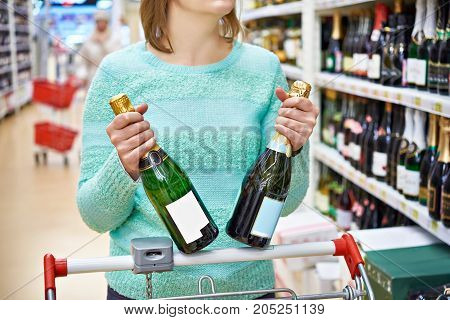 The woman in shop chooses champagne closeup