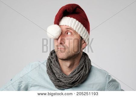 relaxed cauasian mature man wearing santa claus hat looking aside on grey background
