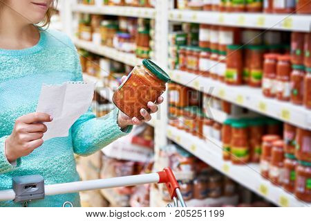 Woman chooses lecho tomato at the grocery store