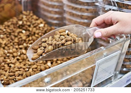 Buyer With Scoop Takes Almond Nuts In Store