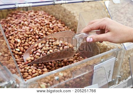 Buyer with scoop takes the peanuts in the store