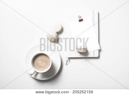 White flat lay with beige macaroons, coffee cup, notepad and postcard mockup on white table background