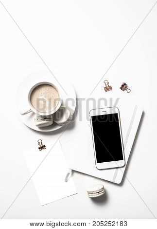 White feminine flat lay with beige macaroons, coffee and smartphone mockup on white table background