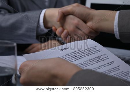Close-up of contract paper with business handshake at the background. Successful negotiation or meeting concept. Low key lighting.