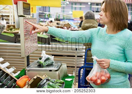 Woman Weighing Cucumbers And Tomatoes In Store