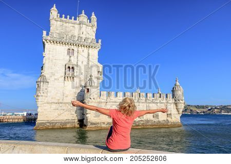 Happy caucasian woman with open arms at Belem Tower. Torre de Belem is Unesco Heritage and symbol of Lisbon, in Belem District on Tagus River. Female tourist enjoys of most visited tourist attraction.