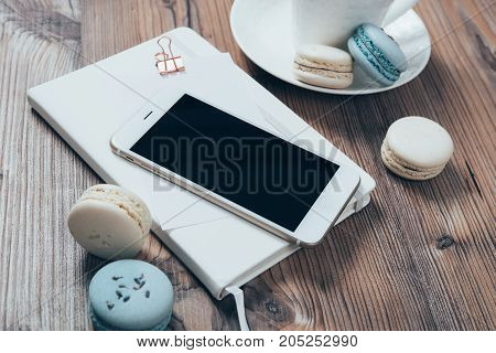 Cup of coffee, blue macaroons and smartphone on wooden table background, bloggers workspace flat lay, phone mockup