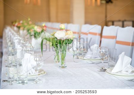 table serving with dishes and flowers in bright hall