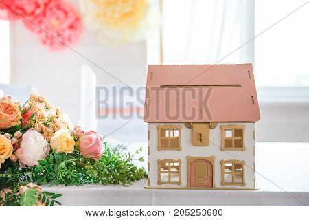 table serving with a little house with flowers, bright background
