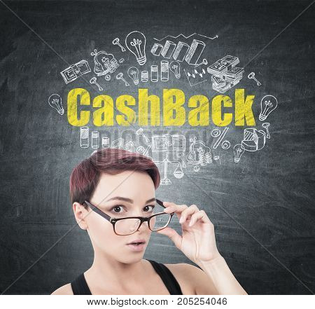 Portrait of a young surprised woman with short red hair taking off her glasses. She is standing near a blackboard with a white and yellow cashback sketch drawn on it.