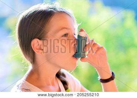 Girl Using Asthma Inhaler In A Park