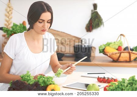 Beautiful  Hispanic or latin american woman is holding wooden spoon while cooking salad  in the kitchen. Brunette housewife searching new recipe by touch pad computer.