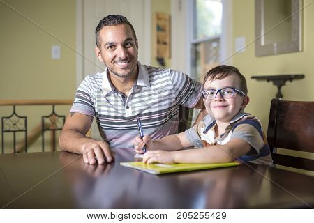 A Father helping son do homework. Parent helps his child