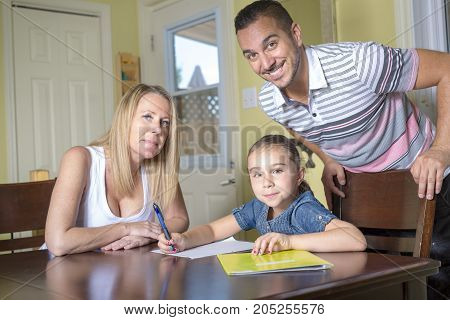 Two parents helping son with homework in home interior