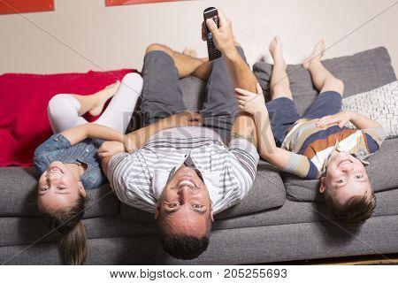 A Family lying upside down on sofa
