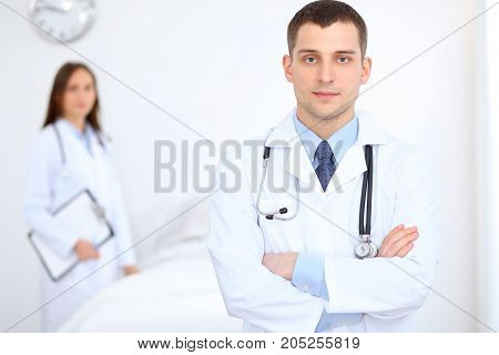Friendly male doctor on the background of female physician in hospital office. Ready to examine and help patients. High level and quality medical service concept. Best treatment and patient care concept