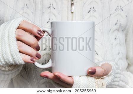 Woman holds white mug in hands. Design Mockup for winter holidays.