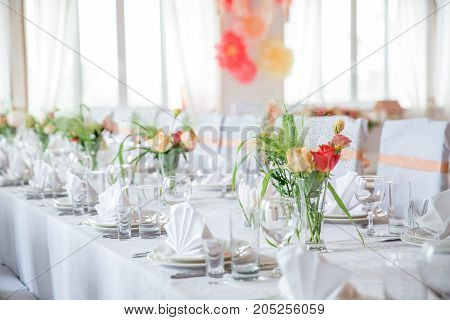 table serving with dishes, glasses and flowers in bright hall
