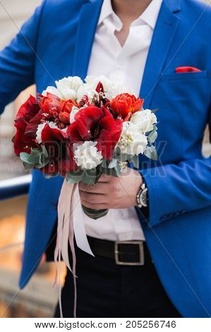 Groom wearing blue jacket holding red and white wedding bouquet