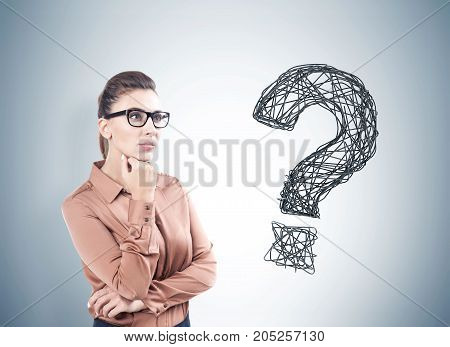Portrait of a pensive young woman with dark hair wearing glasses and a beige blouse. Gray wall background with a large question mark on it.