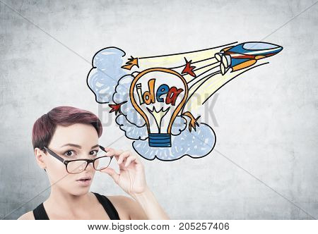 Portrait of a young surprised woman with short red hair taking off her glasses. She is standing near a concrete wall with a colorful idea sketch