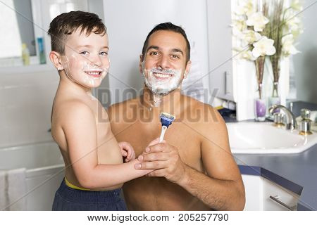 A happy child have fun with dad with shaving foam in the bathroom