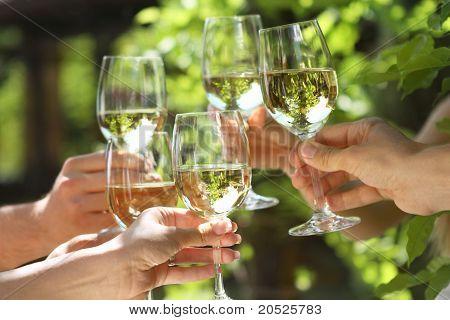 Personas con vasos de vino blanco, hacer un brindis