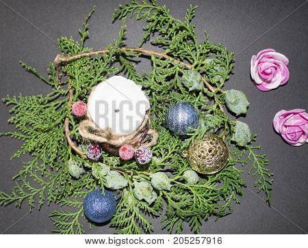 New Year 2018. Background for Christmas and New Year. Green spruce branch with a Christmas ball on a black background. white candle with christmas or Christmas decorations spruce twigs.