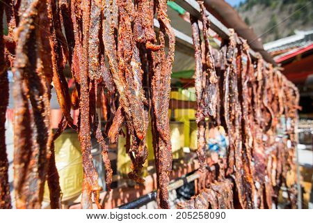 Dried pieces of meat. Hanging meat on the dryer. Dry, raw red meat with spices.