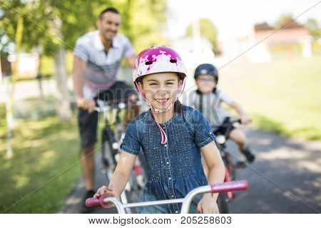 A Dad With Daughter Son Riding Bikes In Park