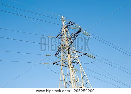 high voltage tower high voltage wires against the blue sky
