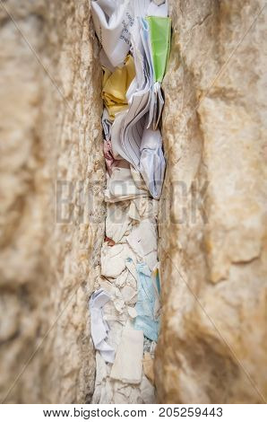 A fragment of the Western wall (Wailing wall) with notes to God in the Old city of Jerusalem, Israel.