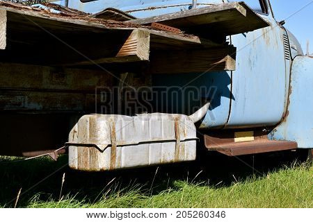 An old pickup with an exposed gas tank hanging under the bed frame, attached to the chassis