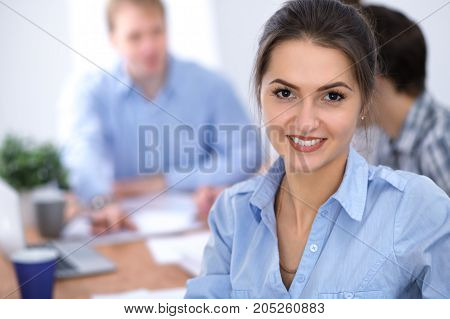 Beautiful business woman on the background of business people during meeting. Casual clothing style. Start up team.