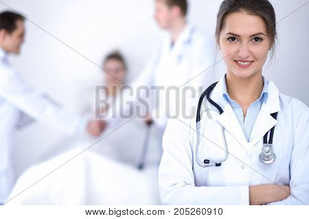 Female doctor smiling on the background with patient in the bed.