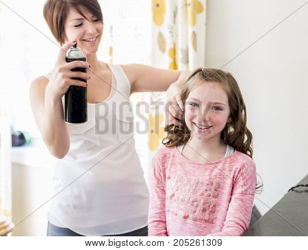 A Mother spray the daughter hair in the kitchen